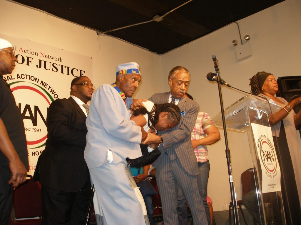 Edaw Garner, the wife of NYPD fatal choking victim, collapses in the arms of Rev. Al Sharpton (right) and Rev. Herbert Daughtry (left) at NAN headquarters in New York. (Photo by Herb Boyd)
