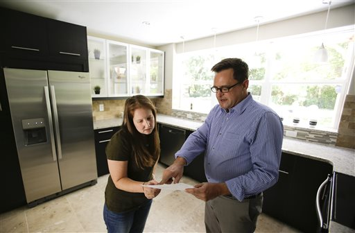 In this Friday, May 23, 2014 photo, realtor Greg Gammonley, right, with ConnectRealty.com, shows off a home to prospective buyer Maddie Coker in Orlando, Fla. A new report released Wednesday, July 16, 2014 by Trulia, the online real estate firm, suggests that the recession — for all its damage to the economy — did little to turn off millennials from the idea of owning a home compared to previous generations. (AP Photo/John Raoux)