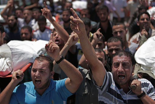 Palestinian mourners chant slogans as they carry the bodies of eight members of the Al Haj family, who were killed in an Israeli missile strike early morning, during their funeral in Khan Younis refugee camp, southern Gaza Strip on Thursday, July 10, 2014. Israel dramatically escalated its aerial assault in Gaza Thursday hitting hundreds of Hamas targets, as Palestinians reported more than a dozen of people killed in strikes that hit a home and a beachside cafe and Israel's missile defense system once again intercepted rockets fired by militants at the country's heartland. (AP Photo/Khalil Hamra)