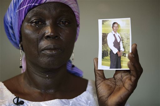 In this Monday, May 19, 2014 file photo, Martha Mark, the mother of kidnapped school girl Monica Mark cries as she displays her photo, in the family house, in Chibok, Nigeria. (AP Photo/Sunday Alamba, File)