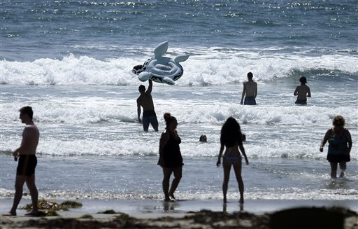 This, June 24, 2014, file photo shows people swimming on a sunny day at Mission Beach in San Diego. Stop sunbathing and using indoor tanning beds, the acting U.S. surgeon general warned in a report that cites an alarming 200 percent jump in deadly melanoma cases since 1973. (AP Photo/Gregory Bull, File)