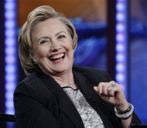 """In this July 15, 2014, photo, former U.S. Secretary of State Hillary Rodham Clinton reacts to host Jon Stewart during a taping of """"The Daily Show with Jon Stewart,"""" in New York. As Clinton promotes her book, liberals in the Democratic party are elbowing into the 2016 presidential conversation while pitching populist messages on the economy and immigration.  (AP Photo/Frank Franklin II)"""
