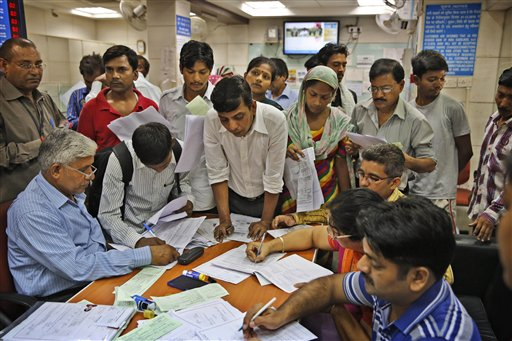 Indians gather around a table inside a state-owned bank to open their accounts as part of a massive countrywide campaign to open millions of accounts for the poor in New Delhi, India, Thursday, Aug. 28, 2014.The measure is aimed at some 150 million Indians who are off the financial grid and vulnerable to black market money lenders. As an incentive the federal government is providing 100,000 rupees ($1,650) in life insurance to every account holder. (AP Photo /Manish Swarup)
