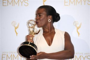 "Uzo Aduba poses in the press room with the award for outstanding guest actress in a comedy series for ""Orange Is the New Black"" at the 2014 Creative Arts Emmys at Nokia Theatre L.A. LIVE on Saturday, Aug. 16, 2014, in Los Angeles. (Photo by Richard Shotwell/Invision/AP)"