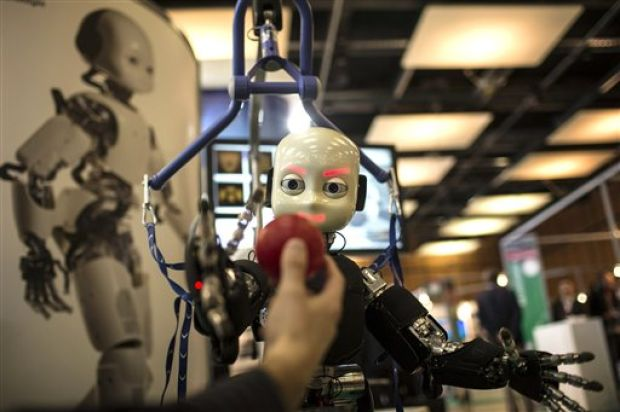 This March 19, 2013, file photo shows the iCub robot trying to catch a ball during the Innorobo European summit, an event dedicated to the service robotics industry, in Lyon, central France. The iCub robot, created by the Italian Institute of Technology, is used for research into human cognition and artificial intelligence. Robots and artificial intelligence could create a near-dystopian income gap, kill all low-skill jobs, or have little impact over the next decade. That according to nearly 2,000 experts surveyed for a new study from Pew Research Center's Internet Project and Elon University's Imagining the Internet Center. (AP Photo/Laurent Cipriani, File)