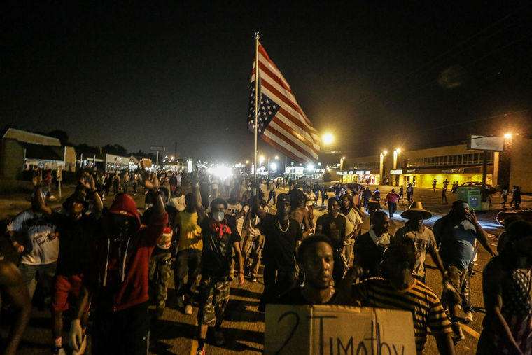 Peaceful protestors rally around the flag in the Ferguson protest zone. (Lawrence Bryant/St. Louis American)