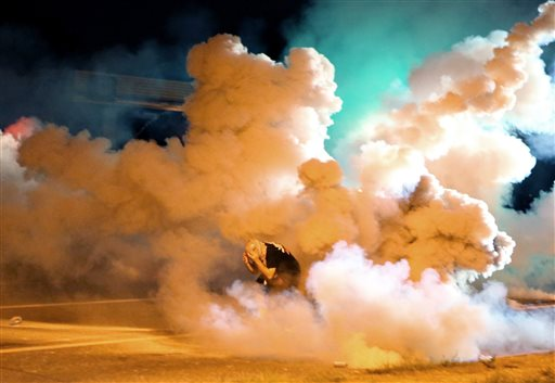 A protester takes shelter from smoke billowing around him Wednesday, Aug. 13, 2014, in Freguson, Mo. Protests in the St. Louis suburb rocked by racial unrest since a white police officer shot an unarmed black teenager to death turned violent Wednesday night, with some people lobbing Molotov cocktails and other objects at police who responded with smoke bombs and tear gas to disperse the crowd. (AP Photo/St. Louis Post-Dispatch, David Carson)