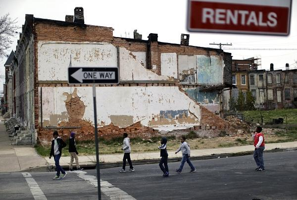 In this April 4, 2013, file photo, a group of boys walk past a partially collapsed row house in Baltimore. The nation's poverty rate stood still at 15 percent in 2012, the sixth straight year that it has failed to improve. The Census Bureau reported Tuesday, Sept. 17, 2013, that 46.5 million Americans were living in poverty in 2012. (AP Photo/Patrick Semansky)