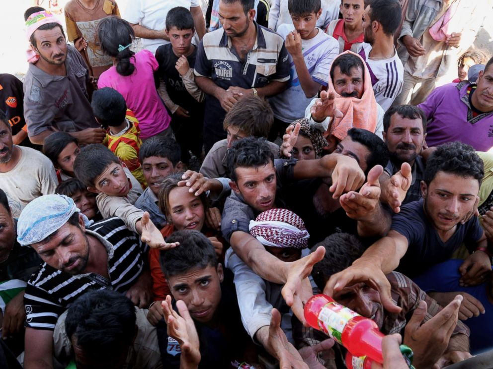 Displaced Iraqis from the Yazidi community gather for humanitarian aid at the Iraq. (Khalid Mohammed/AP)