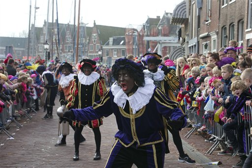 """In this Nov. 16, 2013 file photo a """"Zwarte Piet"""" or """"Black Pete"""", jokes with children after arriving with Sinterklaas, or Saint Nicholas, by steamboat in Hoorn, north-western Netherlands. Amsterdam's mayor and organizers of a large children's winter festival have unveiled plans on Thursday, Aug. 14, 2014 to reform the image of """"Black Pete"""" in order to remove perceived racist elements over a period of years. A large majority of the Netherlands' mostly-white population say Pete is a positive figure and deny any racial insult. But a court and racism experts have found his appearance offensive. (AP Photo/Peter Dejong, File)"""
