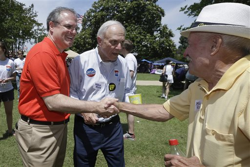 In this file photo taken June 14, 2014, Democratic U.S. Sen. Mark Pryor, left, campaigns for re-election with his father, former U.S. Sen. David Pryor, D-Ark., center, in Warren, Ark. Mark Pryor is reaching into his own medical history to explain his vote on the nation's new health care law, telling Arkansans that his battle with a rare cancer 18 years ago influenced his vote. (AP Photo/Danny Johnston, File)