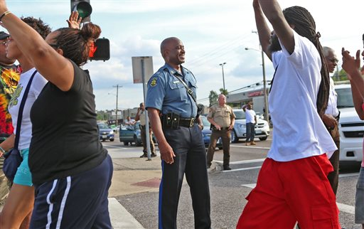 Capt. Ronald Johnson of the Missouri Highway Patrol smiles at demonstrators march along West Florissant Avenue in Ferguson, Mo., on Thursday, Aug. 14, 2014. The Missouri Highway Patrol took control of a St. Louis suburb Thursday, stripping local police of their law-enforcement authority after four days of clashes between officers in riot gear and furious crowds protesting the death of an unarmed black teen shot by an officer. (AP Photo/St. Louis Post-Dispatch, David Carson)