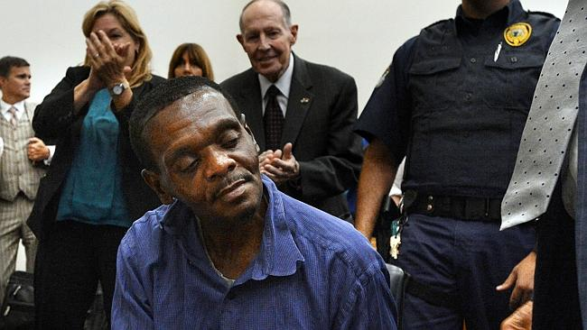 Henry McCollum sits quietly as thunderous applause rings out around him in a Robeson County courtroom. (AP Photo)