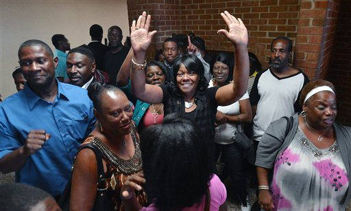 Geraldine Brown, sister of Leon Brown, celebrates outside a Robeson County courtroom where her brothers were declared innocent of the rape and murder of an 11 year old girl in 1983, Tuesday, Sept. 2, 2014 in Lumberton, N.C. On Tuesday, a judge overturned the convictions of Henry McCollum, 50, and Leon Brown, 46, in the 1983 rape and murder of the 11-year-old girl, citing the new evidence that they are innocent. The ruling is the latest twist in a notorious legal case against the men that began with what defense attorneys said were coerced confessions from two scared teenagers with low IQs. (AP Photo/The News & Observer, Chuck Liddy)