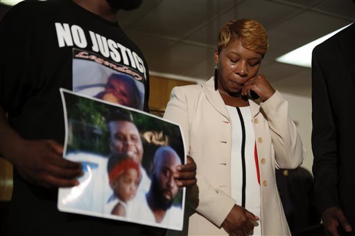 In this Aug. 11, 2014 file photo, Lesley McSpadden, the mother of 18-year-old Michael Brown, wipes away tears as Brown's father, Michael Brown Sr., holds up a family picture of himself, his son, top left, and a young child during a news conference in Jennings, Mo. Lingering questions about Michael Brown could be answered Wednesday as two news organizations seek the release of any possible juvenile records for the unarmed 18-year-old who was shot by a police officer last month. (AP Photo/Jeff Roberson, File)