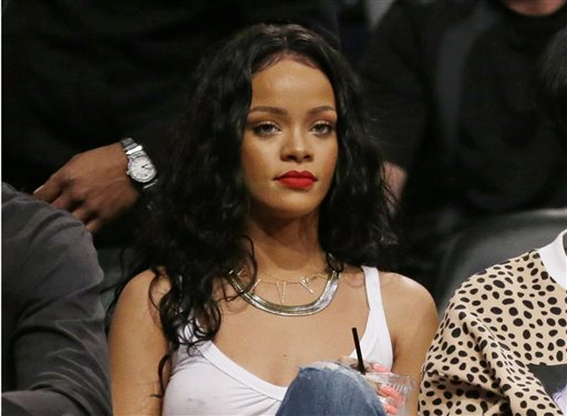 "FILE - This April 25, 2014 file photo shows singer Rihanna watching Game 3 of an NBA basketball first-round playoff series between the Brooklyn Nets and the Toronto Raptors in New York. CBS said Tuesday, Sept. 16, 2014 it was permanently editing a song featuring Rihanna's voice out of its Thursday night NFL telecasts _ after the singer issued a profane tweet about it. A portion of Jay-Z's ""Run This Town"" featuring Rihanna was cut out of last Thursday's game because the network was covering the controversy over Rice's assault of his then-fiancee. CBS had planned to use the song Thursday and for the rest of the season, but Rihanna tweeted her objections. CBS issued a statement saying that it was ""moving in a different direction"" with different theme music. (AP Photo/Frank Franklin II, File)"