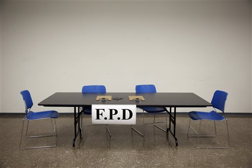 A table sits ready to be used by members of the Department of Justice before meeting with people individually about their interactions with the Ferguson police department and other law enforcement agencies in St. Louis County Wednesday, Sept. 24, 2014, in Ferguson, Mo.  After updating the gathered crowd on the federal agency's investigation of Ferguson police, members of the DOJ spoke privately with people about their experiences. (AP Photo/Jeff Roberson)