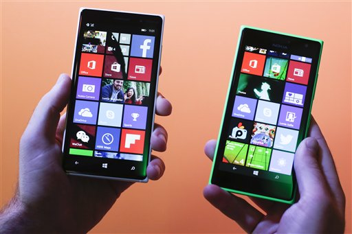 A man shows the new Lumia 830, left, and 730, right, smart phones during a Microsoft Nokia  presentation event at the consumer electronic fair IFA in Berlin, Thursday, Sept. 4, 2014. (AP Photo/Markus Schreiber)