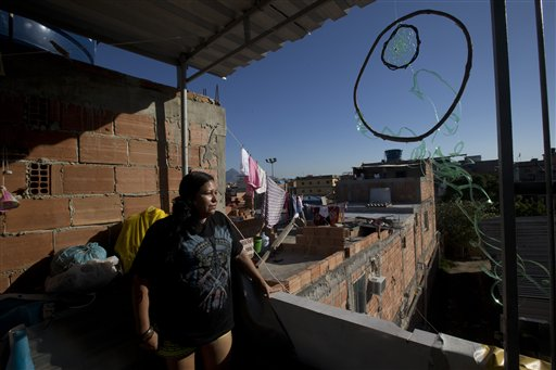In this Aug. 24, 2014 photo, Vieira a Guarani indian gets a view of the Mare slum, next to a dream catcher hanging from the roof, in Rio de Janeiro, Brazil. Some 5,000 indians from across Brazil live in Rio's favelas, where many of them fight to keep their traditions alive amidst grinding poverty and rampant violence. (AP Photo/Silvia Izquierdo)