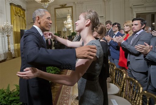 President Barack Obama, left, steps off stage to hug Lilly Jay, right, a sexual assault survivor, during a 'It's On Us' campaign event in the East Room of the White House in Washington, Friday, Sept. 19, 2014.  Obama spoke Friday as the White House unveiled a new campaign to change the way people think about campus sexual assault.  (AP Photo/Pablo Martinez Monsivais)