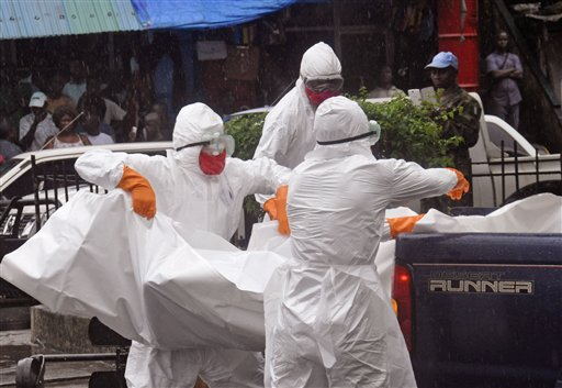 Health workers load the body of an amputee suspected of dying from the Ebola virus during the rain on the back of a truck, in a busy street in Monrovia, Liberia, Tuesday, Sept. 2, 2014.  Food in countries hit by Ebola is getting more expensive and will become scarcer because many farmers won't be able to access fields, a U.N. food agency warned Tuesday. An Ebola outbreak in West Africa has killed more than 1,500 people, and authorities have cordoned off entire towns in an effort to halt the virus' spread.  (AP Photo/Abbas Dulleh)