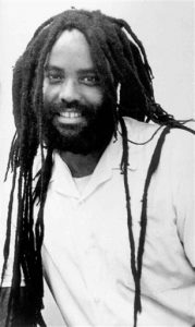 This undated file photo shows convicted police killer Mumia Abu-Jamal. Goddard College, a liberal arts college in Plainfield, Vt., with 600 students, said  on its website Tuesday, Sept. 30, 2014, that Mumia Abu-Jamal's recorded remarks will be played Sunday at a commencement, along with a video about him. (AP Photo/Jennifer E. Beach, File)