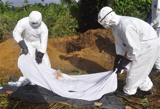 In this photo taken on Monday, Oct. 27, 2014, health workers prepare to place the body of a man who was suspected of dying from the Ebola virus into a grave on the outskirts of Monrovia, Liberia. The head of Africa's continental body did not get to an Ebola-hit country until last week - months after alarm bells first rang and nearly 5,000 deaths later. (AP Photo/Abbas Dulleh)