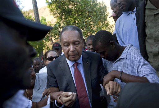 "In this Feb. 8, 2011 file photo, former Haitian dictator Jean-Claude ""Baby Doc"" Duvalier's supporters help him negotiate an uneven path during a visit to his mother's hometown and grave site in Leogane, Haiti. (AP Photo/Ramon Espinosa, File)"