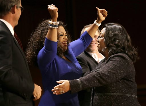 Actor, talk show host and philanthropist Oprah Winfrey, center left, and television producer and writer Shonda Rhimes, right, embrace on stage during the W.E.B. Du Bois medal award ceremonies, Tuesday, Sept. 30, 2014, on the campus of Harvard University, in Cambridge, Mass. The Du Bois Medal is Harvard's highest honor in the field of African and African American Studies. Winfrey and Rhimes both received the medal. (AP Photo/Steven Senne)