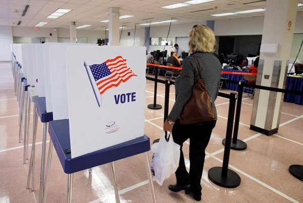 A woman walked past voting booths at the Cuyahoga County Board of Elections in Cleveland on Tuesday. (Mark Duncan/AP Photo)