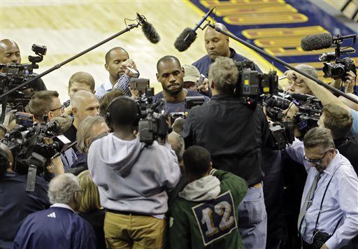 Cleveland Cavaliers' LeBron James, center, is besieged by the media after practice Wednesday, Oct. 29, 2014, in Cleveland. It will be a night unlike any in Cleveland sports history as LeBron James returns to play his first NBA regular-season game for the Cavaliers in four years. Any bitterness toward James has been replaced with forgiveness by a city thirsting for a championship. (AP Photo/Mark Duncan)