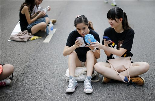 Student pro-democracy activists use their smartphones while sitting on the streets near the government headquarters, Thursday, Oct. 2, 2014 in Hong Kong. The Chinese government might be using smartphone apps to spy on pro-democracy protesters in Hong Kong, a U.S. security firm says. The applications are disguised as tools created by activists to protests, said the firm, Lacoon Mobile Security. The firm said that once downloaded, they give an outsider access to the phone's address book, call logs and other information. (AP Photo/Wong Maye-E)