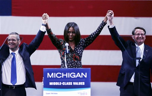 First lady Michelle Obama stands with Michigan gubernatorial candidate Mark Schauer, left, and Senate candidate, Rep. Gary Peters during a campaign rally for them in Detroit, Friday, Oct. 10, 2014. Michelle Obama came to heavily Democratic Detroit Friday afternoon to rally support for Peters, a suburban Detroit congressman hoping to succeed retiring Democrat Sen. Carl Levin after 36 years in office.  (AP Photo/Carlos Osorio)