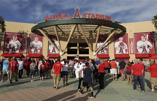 In this Oct. 3, 2014, file photo, fans enter Angel Stadium of Anaheim before Game 2 of baseball's AL Division Series between the Los Angeles Angels and the Kansas City Royals in Anaheim, Calif. In Southern California, police are looking Monday, Oct,. 6 for three men suspected of brutally beating a man in the Angels Stadium parking lot after the Angels' playoff night game on Friday, Oct. 3. (AP Photo/Gregory Bull, File)
