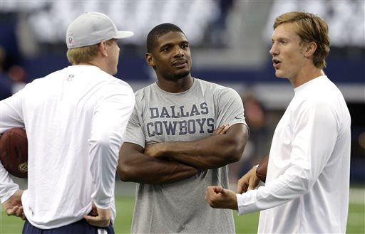 In this Sept. 7, 2014, file photo, Dallas Cowboys Michael Sam, center, talks on the field before the start of an NFL football game against the San Francisco 49ers in Arlington, Texas. The Cowboys have released Michael Sam from the practice squad, Tuesday, Oct. 21, 2014, another setback as the NFL's first openly gay player tries to make an active roster during the regular season for the first time. (AP Photo/LM Otero, File)