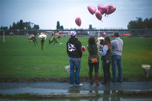 A memorial grows Saturday Oct. 25, 2014 at the entrance to Marysville Pilchuck High School the day after a shooting in the school cafeteria left two dead and four wounded. The shooter was among the dead. A first year teacher was being hailed as a hero for intervening in the shooting, possibly stopping the gunman. (AP Photo/seattlepi.com, Joshua Trujillo)