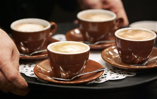 In this Friday, Feb. 6, 2009 photo, the owner of a coffee shop serves cappuccinos to judges during a barista competition in Cranberry, Pa. Scientists have long known that one's genes influence how much of coffee one consumes, and a study released Tuesday, Oct. 7, 2014 by the journal Molecular Psychiatry has identified some genes that may play a role. Their apparent effect is quite small. But variations in these genes may modify coffee's effect on a person's health, and so such genetic research may help scientists explore that, said Marilyn Cornelis of the Harvard School of Public Health. (AP Photo/Keith Srakocic)