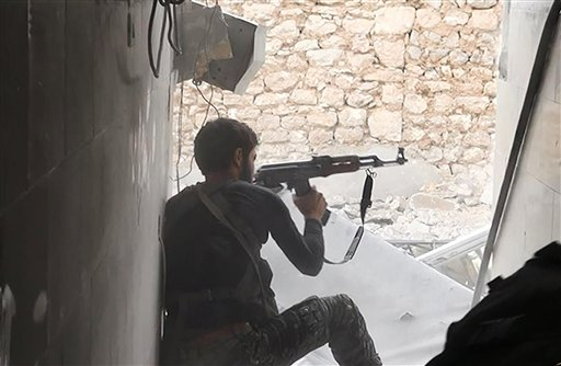This undated file photo posted on Monday, Nov. 4, 2014 by the Raqqa Media Office of the Islamic State group, a militant extremist group, shows an Islamic state group fighter in Kobani, Syria. For a force that has built its reputation on projecting an aura of momentum and invincibility, the prolonged stalemate in Kobani is a setback for Islamic State militants with potential implications in terms of recruitment and support. Nearly two months after it launched its lightning assault on the small Kurdish town, the group is bogged down with an increasingly entrenched and costly battle in which hundreds of its fighters have been killed and a good deal of its military apparatus destroyed. (AP Photo/Raqqa Media Office, File)