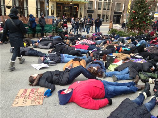 About 200 people demonstrate at a plaza near the historic water tower, located along Chicago's Michigan Avenue, on Friday, Nov. 28, 2014, in Chicago. The protestors called on people to boycott shopping on Black Friday as a show of solidarity with protesters in Ferguson Missouri. At one point the demonstrator lay down on the cold ground in a silent protest. (AP Photo/Sara Burnett)