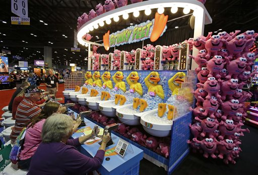 "In this Tuesday, Nov. 18, 2014 file photo, trade show attendees compete at a water game called Stinky Feet at the International Association of Amusement Parks and Attractions convention and trade show in Orlando, Fla. The annual International Association of Amusement Parks and Attractions Expo is a massive industry trade show. the real buzzword at the show is ""interactivity."" It seems that every vendor and park owner is seeking to somehow merge thrill rides with video games. (AP Photo/John Raoux, File)"