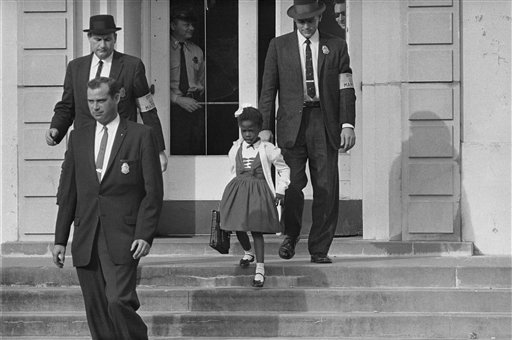 In this Nov. 1960 file photo, U.S. Deputy Marshals escort six-year-old Ruby Bridges from William Frantz Elementary School in New Orleans, La.  The first grader was the only black child enrolled in the school, where parents of white students were boycotting the court-ordered integration law and were taking their children out of school. Ruby Bridges will be one of the presenting authors at this weekend's New Orleans Children's Book Festival, an event Bridges helped launch in 2010. (AP Photo, file)