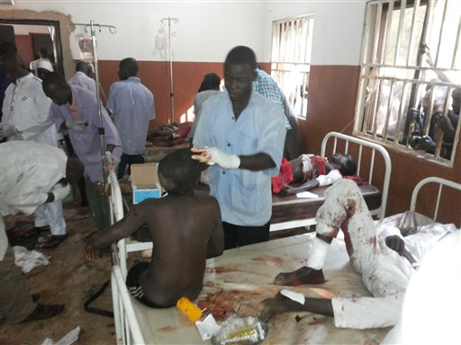 People are treated at the General hospital in Potiskum, Nigeria, Monday, Nov. 10, 2014, following a suicide bomb attack at Government Science Technical College Potiskum. Survivors say a suicide bomber disguised in a school uniform has detonated explosives at a high school assembly in northeast Nigeria, and a morgue worker says 48 students have been killed. (AP Photo/Adamu Adamu)
