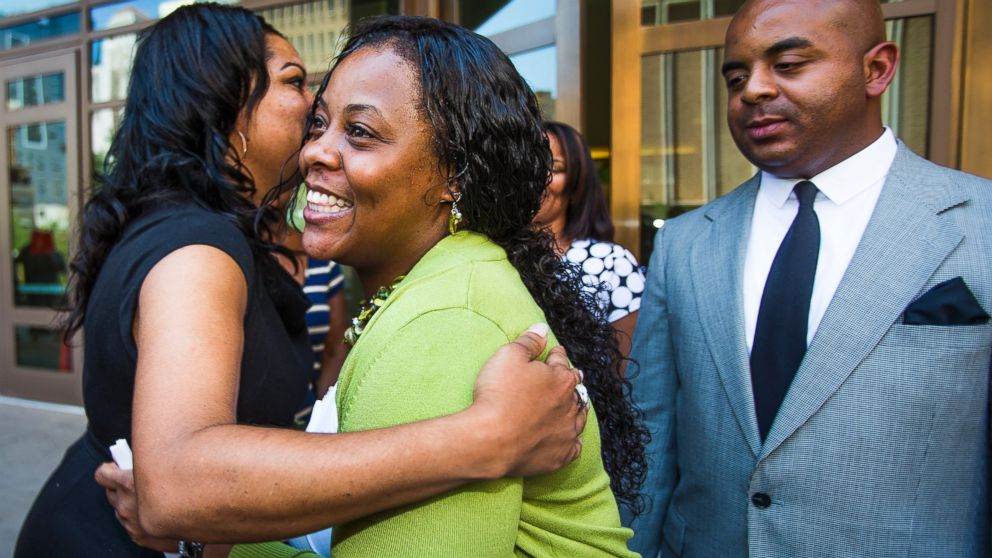 Shanesha Taylor is hugged as Rev. Jarrett Maupin looks on, outside Maricopa County Superior Court, July 18, 2014 in Phoenix. (Tom Tingle/The Arizona Republic/AP Photo)