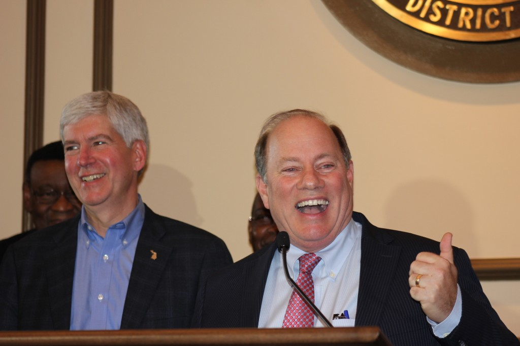 Gov. Rick Snyder and Mayor Mike Duggan celebrated Bankruptcy Judge Steven Rhodes' acceptance of their Plan of Adjustment that cuts workers' and retirees' pensions and healthcare, and takes back earlier annuity payments from the city over the last decade. (Curt Guyette/Michigan Citizen)