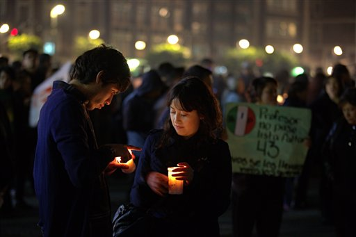 """A couple hold candles during a massive protest in Mexico City's main sqaure """"El Zocalo,"""" during a march in the capital city to demand authorities find 43 missing college students, in Mexico City, Thursday Nov. 20, 2014. Mexico officially lists more than 22 thousand people as having gone missing since the start of the country's drug war in 2006, and the search for the missing students has turned up other, unrelated mass graves. in Mexico City, Thursday, November 20, 2014. (AP Photo/Eduardo Verdugo)"""