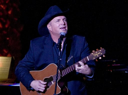 """In this Nov. 17, 2014 file photo, Garth Brooks performs the 2014 ASCAP Centennial Awards, benefiting the ASCAP Foundation and its music education, talent development and humanitarian activities, at the Waldorf-Astoria in New York. Brooks has canceled a Thanksgiving appearance on NBC's """"Tonight"""" show because he said it """"seemed distasteful"""" given the reaction to the decision not to prosecute Ferguson police officer Darren Wilson for the shooting of Michael Brown this summer. NBC on Wednesday, Nov. 26, confirmed the postponement, saying Brooks was being replaced on the show by Whoopi Goldberg and Tom Colicchio. (Photo by Stephen Chernin/Invision/AP, File)"""