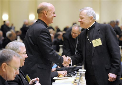 Bishop Kevin C. Rhoades, left, of Fort Wayne-South Bend, Ind., and Archbishop Gregory M. Aymond of New Orleans shake hands at the start of a U.S. Conference of Catholic Bishops general meeting at the conference's annual fall meeting in Baltimore, Monday, Nov. 10, 2014. (AP Photo/Steve Ruark)