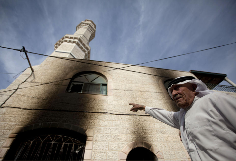 A Palestinians inspects damages of a mosque following an attack in the West Bank village of Mughayer, north of Ramallah, Wednesday, Nov. 12, 2014. An attack against a mosque in a West Bank village early on Wednesday ignited a fire that destroyed its first floor, the village's mayor said, blaming Jewish settlers for the attack. (AP Photo/Majdi Mohammed)
