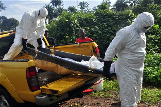 In this Oct. 27, 2014 file photo, health workers unload the lifeless body of a man suspected of contracting the Ebola virus, as they carry him to a grave site on the outskirts of Monrovia, Liberia. Health officials in the U.S. and Europe are scrambling to begin testing a handful of experimental Ebola drugs in Africa, but an ethical debate is brewing over how to appropriately test medicines amid an outbreak that has already killed nearly 5,000 people. (AP Photo/Abbas Dulleh, File)