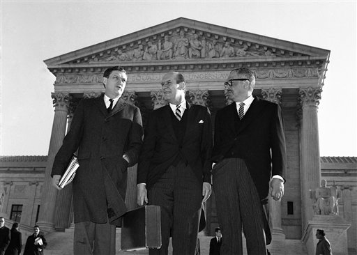 In this Jan. 17, 1966 file photo, Assistant Attorney General John Doar, left, stands with Attorney General Nicholas Katzenbach, center, and Solicitor General Thurgood Marshall as they arrive at the Supreme Court building in Washington to defend the legality of the 1965 Voting Rights Act. Doar, who as a top Justice Department civil rights lawyer in the 1960s fought to protect the rights of black voters and integrate universities in the South, died Tuesday, Nov. 11, 2014 at the age of 92.  (AP Photo)
